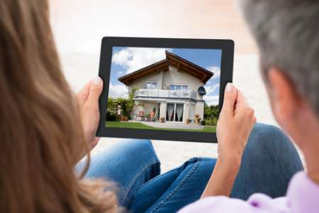 Picture of a couple looking at a house on a tablet.