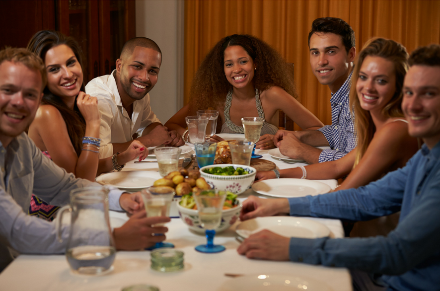 Group of people sitting at a dinner table smiling and laughing.